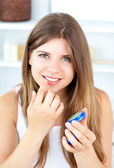 Radiant woman using cosmetic cream in a bathroom — Stock Photo