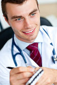 Attractive male doctor writing a perscription — Stock Photo