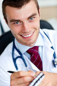 Smiling male doctor writing a perscription — Stock Photo