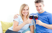 Cute couple drinking wine together in the living-room — Stock Photo
