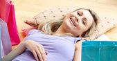 Brillante donna relax dopo lo shopping circondato con borse della spesa a casa — Foto Stock