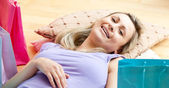 買い物袋を自宅でショッピングに囲まれて後にリラックスできる明るい女性 — ストック写真