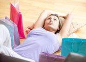Mooie vrouw ontspannen na winkelen met boodschappentassen thuis omgeven — Stockfoto