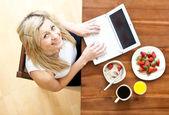 自宅で朝食をとりながら、ラップトップを使用してきれいな女性 — ストック写真