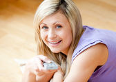 Smiling young woman watching TV lying on the floor at home — Stock Photo
