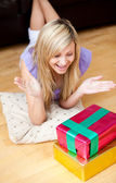 Surprised young woman opening gifts lying on the floor in the living-room — Stock Photo