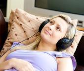 Fröhliche frau hört die musik in die wohnzimmer im homewoman — Stockfoto