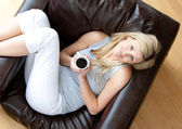 Charming woman drinking coffee sitting on a sofa in a living-room — Stock Photo