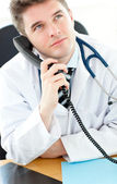 Handsome male doctor talking on the phone in his office — Stock Photo