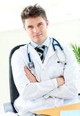 Retrato de un seguro médico self-assured sosteniendo un estetoscopio contra un fondo blanco — Foto de Stock