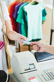 Close-up of a cute woman paying with her credit card — Stock Photo