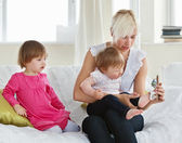 Smiling mother playing with her daughters — Stock Photo