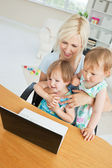 Radiant woman working with her children at laptop — Stock Photo
