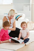 Good-looking woman working with her children at laptop — Stock Photo