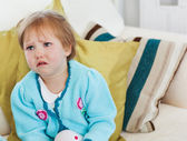 Small girl crying on sofa — Stock Photo