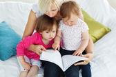 Schattig moeder lezen van een boek met kinderen — Stockfoto