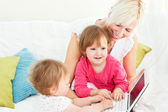 Smiling woman working with her children at laptop — Stock Photo
