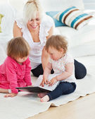 Pretty woman working with her children at laptop — Stock Photo