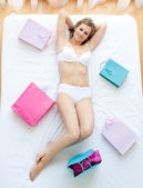 Erotic woman lying in bed with shopping bags — Stock Photo