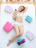 Nice woman lying in bed with shopping bags — Stock Photo