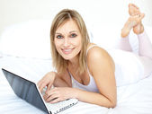 Attractive woman lying with a laptop on sofa — Stock Photo
