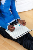 Woman using a laptop sitting on bed — Stock Photo