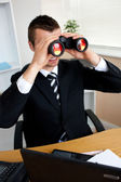 Businessman using binoculars — Stock Photo