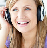 Laughing woman listening to music — Stock Photo
