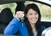 Radiant teenager holding car keys sitting in her new car — Stock Photo
