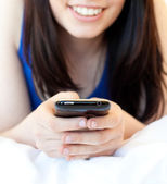 Close-up of a brunette teenager texting while lying on her bed — Stock Photo