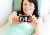 Attractive woman taking a picture of herself lying on bed — Stock Photo