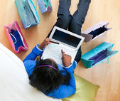 Pretty afro-american teenager using a laptop sitting between sho — Stock Photo