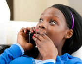 Astonished afro-american teenager talking on phone — Stock Photo
