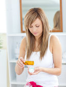 Serious woman taking pills in the bathroom — Stock Photo