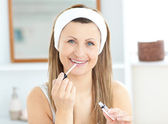 Glowing woman applying gloss on her lips wearing a headband — Stock Photo