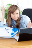 Irritated businesswoman looking at her laptop — Stock Photo
