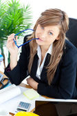 Thougtful businesswoman holding glasses sitting at her desk — Stock Photo