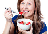 Positive young woman eating cereals with strawberries — Stock Photo