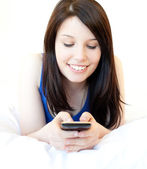 Happy female teenager using cellphone lying on the bed — Stock Photo