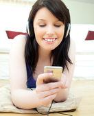 迷人的年轻女子听音乐躺在地板上 — 图库照片