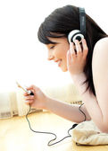 Jolly young woman listen to music lying on the floor — Stock Photo