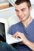 Joyful young man sitting on the sofa using his laptop — Stock Photo