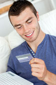 Attractive young man holding a card and a latop sitting on the s — Stock Photo