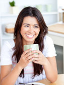 Beautiful asian woman holding a cup sitting in the kitchen — Stock Photo