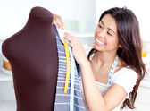 Glowing young woman working with clothes — Stock Photo