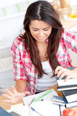 Frustrated asian student doing her homework — Stock Photo