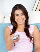 Captivating asian woman holding a remote smiling at the camera — Stock Photo