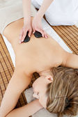 Pretty woman lying on a massage table having a stone therapy — Stock Photo