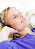 Relaxed woman listen to music lying on a sofa — Stock Photo