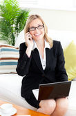 Ambitious businessowman talking on phone using her laptop — Stock Photo